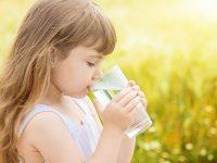 Das Mädchen hält das Wasserglas und trinkt